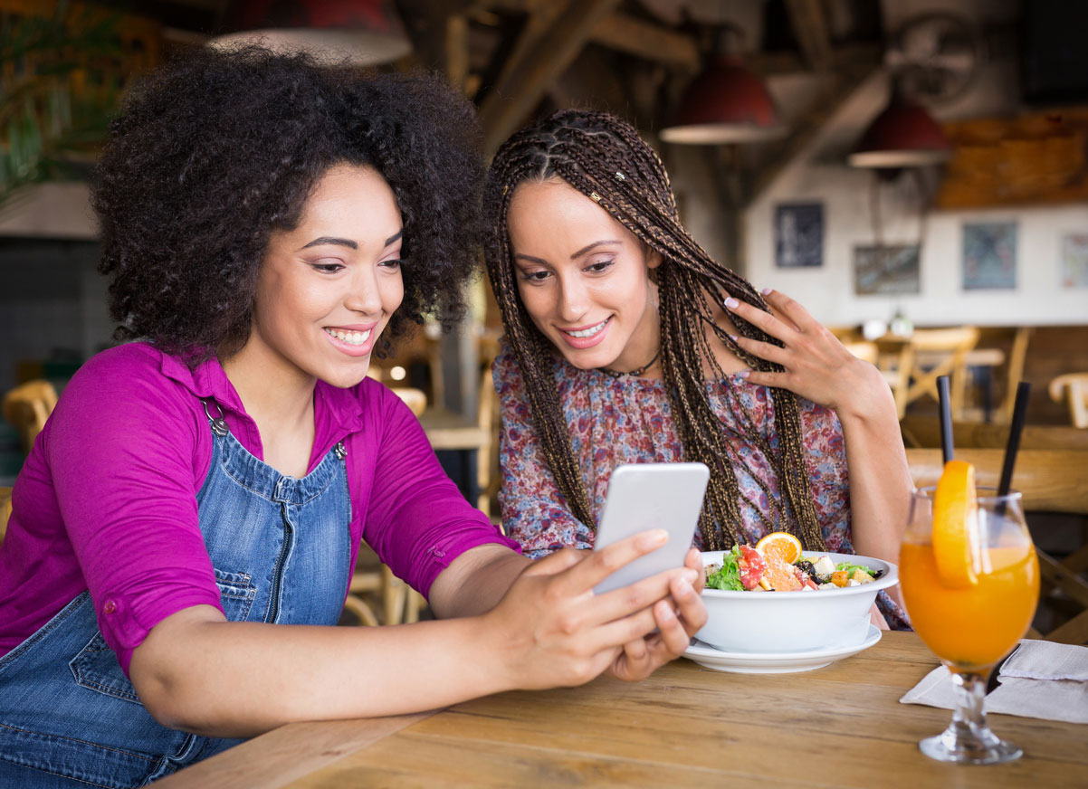 Freundinnen-unterwegs-mit-Smartphone